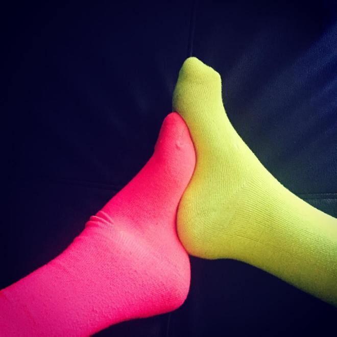 Two high arched feet in neon socks, one pink and one yellow, interlock.